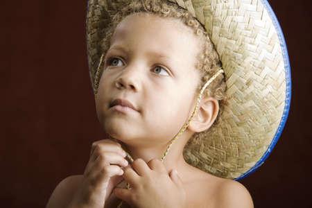 chapeau de paille: Petit gar�on aux cheveux boucl�s et les yeux bleus dans un chapeau de paille