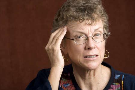 Senior woman with a headache rubbing her temple Stock Photo