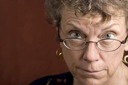 skeptic: Senior woman looking over the top of her glasses Stock Photo
