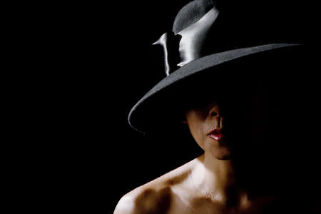 retro woman: Mysterious woman in shadows wearing  vintage black hat Stock Photo