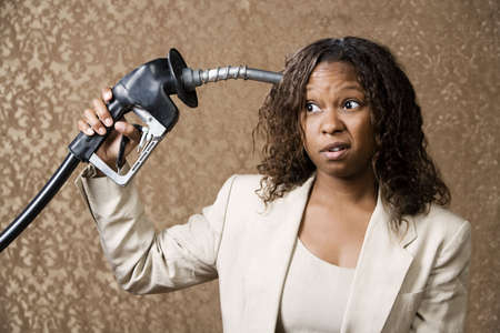dismay: Woman holding gas nozzle like a gun to her head Stock Photo