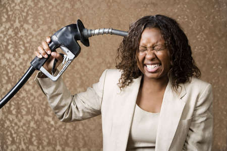 Woman holding gas nozzle like a gun to her head Stock Photo