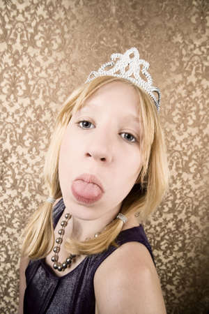 rude: Portrait of pretty pouting young girl wearing a tiara with her tongue out Stock Photo