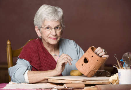 Senior woman working on a clay sculpture