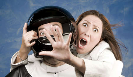 ady: Man and fearful woman on a motorcycle in studio