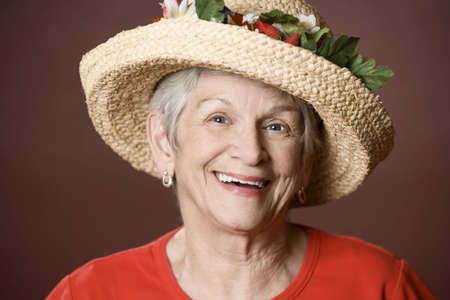 Senior woman in a red shirt and straw hat Stock fotó
