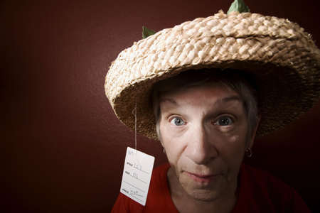 Senior woman in a red shirt and cheap straw hat Stock fotó