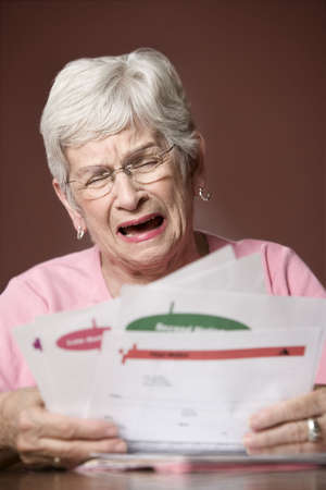 Upset senior woman with many bills and notices