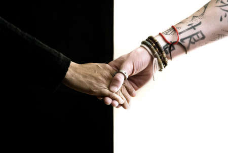 grasp: Close up of black and white hands holding each other
