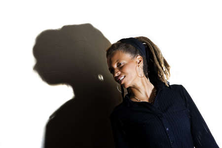 African American woman with dreadlocks against a white wall Stock Photo
