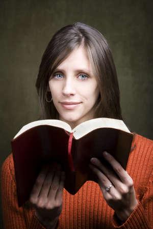 Pretty woman in orange sweater with Bible