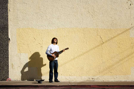 Young man on street with guitar and hat photo