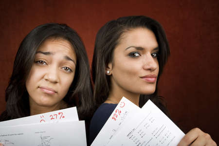 scores: Two girls with conrasting scores on school tests