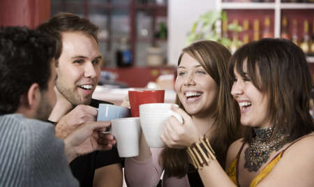 Young toasting friends with coffee cups in a cafe Archivio Fotografico
