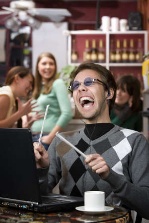 annoy: Obnoxious young man singing loudly in a coffee house Stock Photo