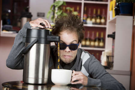 Young man crazily pouring coffee from a thermos in a cafe photo