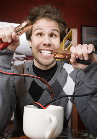 maniacal: Young man holding jumper cables coming out of coffee mug Stock Photo