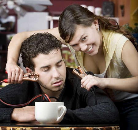 jolt: Young woman holding jumper cables coming out of coffee mug to mans head Stock Photo
