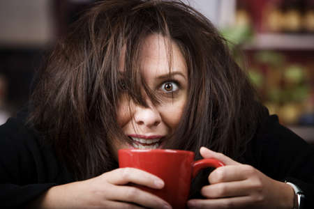 crazed: Half awake woman cradling a mug of coffee