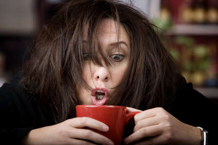 コーヒーのマグカップをあやし半分目を覚まし女性