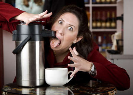 Woman drinking coffee directly from a beverage dispenser