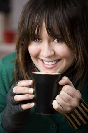 Pretty Young Girl with Coffee in a Mug and Foam on her Lip photo