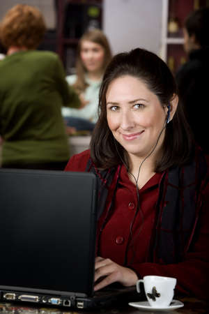Hispanic woman in a cafe with earphones and a laptop computer photo