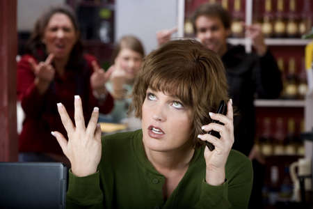 Annoying woman in a cafe on her cell phone gets the finger Stock Photo