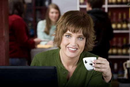 Pretty woman in a cafe with earphones and a laptop computer photo