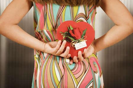 Little girl holding a Valentine behind her back