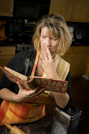 harried: Harried woman in residential kitchen with recipe book