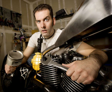crescent wrench: Overwhelmed man in residential garage working on chopper-style motorcycle