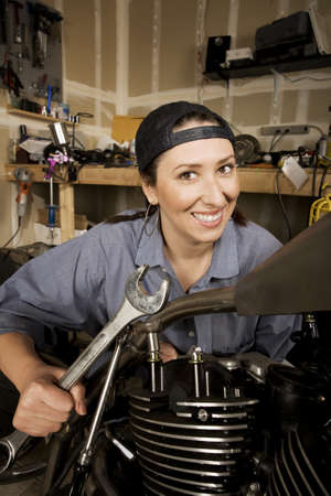 capable: Female Hispanic mechanic working on a chopper style motorcycle