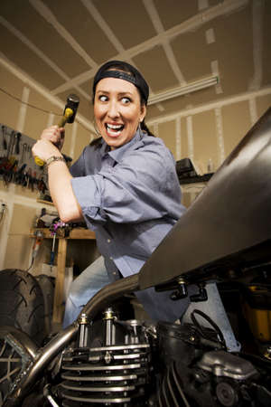 crazed: Hispanic woman swinging a sledgehammer at a motorcycle