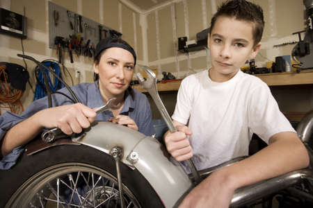 Hispanic mother and son working on motorcycle in garage photo