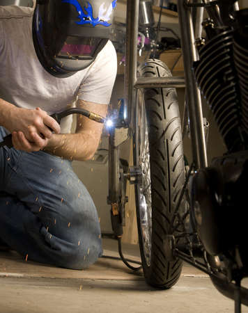 Welder working on the metal fork of a motorcycle