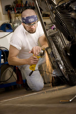 Hispanic man using grinder tool on the front fork of motorcycle Banco de Imagens