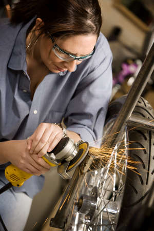 Hispanic womman using grinder tool on the front fork of motorcycle photo