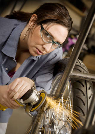 Hispanic woman using grinder tool on the front fork of motorcycle photo