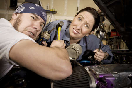 unskilled: Hapless mechanics working on car with all the wrong tools Stock Photo