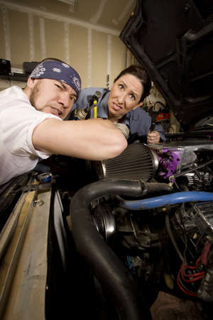 Hapless mechanics working on car with all the wrong tools photo