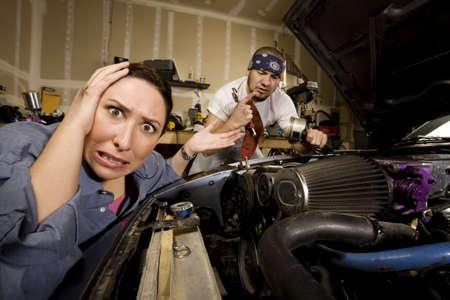 novios enojados: Frustrado mujer apoy�ndose en autom�vil con hombres incompetentes mec�nico en el fondo Foto de archivo