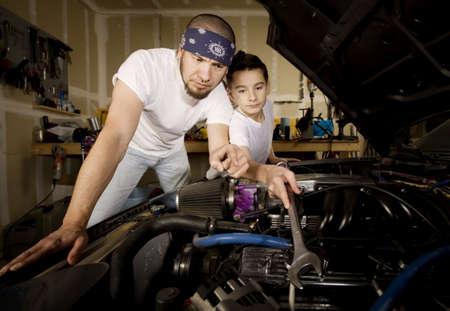 garage: Hispanic father and son working on car engine in garage