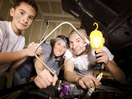 unskilled: Hapless family of mechanics working on car with all the wrong tools