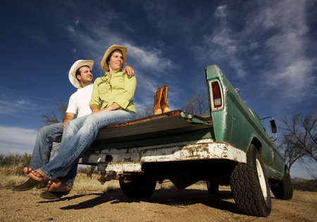 barefoot cowboy: Portrait of Cowboy and woman on pickup truck bed