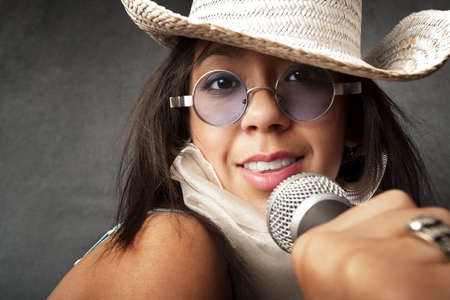 Pretty young singer with a large microphone photo