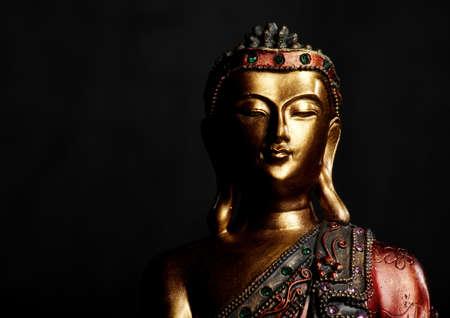 Golden Buddha statue on a dark background