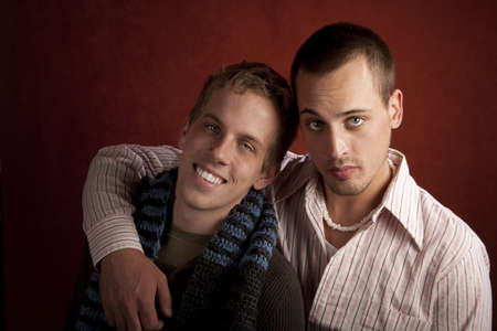 Portrait of two young men embracing in studio