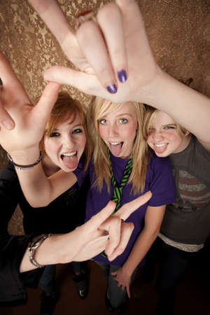 Portrait of three pretty young girls on a gold background making bull horn gestures photo