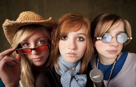 Portrait of three pretty young girls with a microphone on green background photo